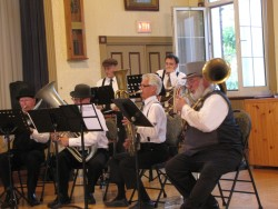 (from left to right) Members of the Orono Cornet Band playing rotary valve trombone, bass saxhorn, ophicleide and helicon.