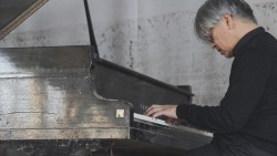 Sakamoto playing the tsunami piano.